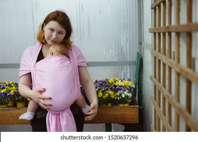 Mother carrying sleeping infant daughter in a sling wrap. Babywearing while running errands and shopping in a greenhouse.