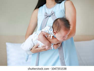 Mother carrying upside down infant baby for decrease baby Flatulence. Baby health care concept.