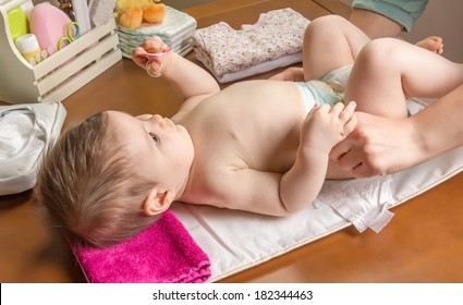 Mother changing diaper of adorable baby with a hygiene set for babies on the background