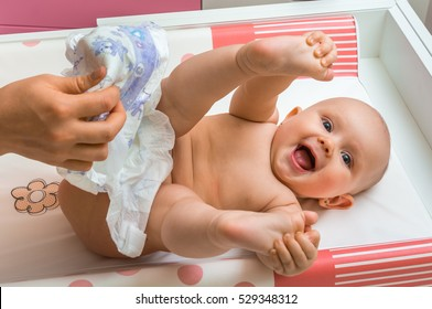 Mother changing diaper to her little baby girl in child room at home