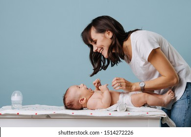 Mother changing diaper on her baby on table over blue background. They look at each other, smile and laugh.