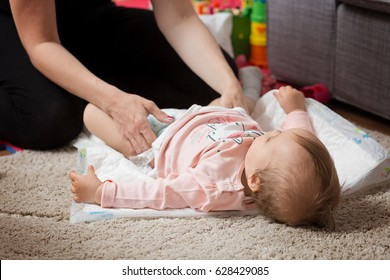 Mother changing diapers of a one year old baby girl daughter; child laying on the floor carpet in the living room with toys in the background; mother's hands visible