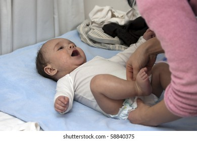 A mother changing her baby boy's nappy whilst laying on a blue blanket and wearing a white vest.