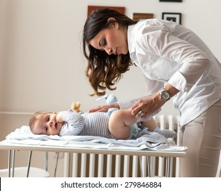 Mother changing her baby diapers.