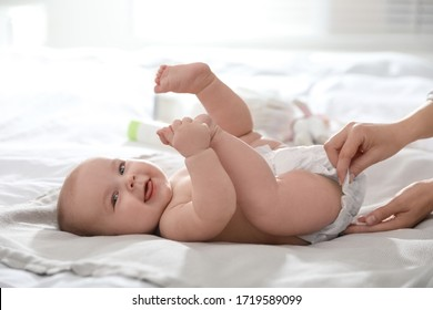Mother changing her baby's diaper on bed