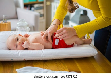 Mother changing reusable diaper or nappy. Reusable diaper and infant. Baby with eco diaper.