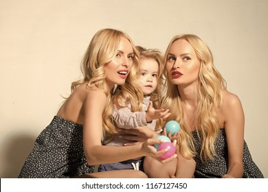 mother and child with aunt, happy family of twins women and small boy son paly with toy balls, childhood and motherhood, happiness