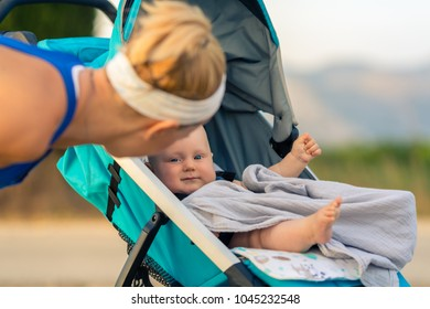 Mother with child in baby stroller enjoying motherhood at sunset and mountains landscape. Jogging or power walking woman with pram at sunset. Beautiful inspirational mountains landscape.