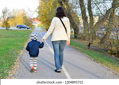 Mother and child boy holding each other hand and walking on autumn street to home from kindergarten back view. Family and parenthood concept.