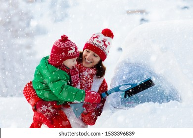 Mother and child brushing and shoveling snow off car after storm. Parent and kid with winter brush and scraper clearing family car after overnight snow blizzard. Christmas vacation in the mountains.