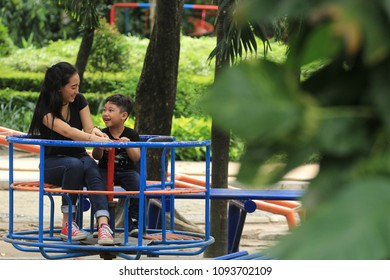 a mother and child are busy joking together in one of the parks in the city tasikmalaya west java Indonesia. this is one of the love and affection of mother to her child. photoshoot on April 13, 2017.