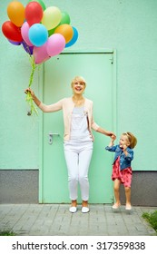 mother and child with colorful balloons on green background