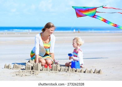 Mother and child concept: young beautiful woman and her lovely cute toddler daughter playing together on the beach building sand castles and flying colorful kite, North Sea, Belgian coast