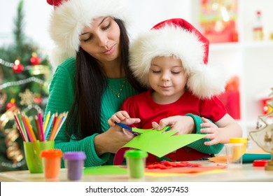 Mother and child cut christmas tree from paper preparing to holiday