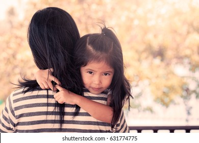 Mother and child cute little girl resting on her mother's shoulder in vintage color tone