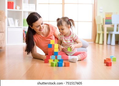 Mother and child daughter building from toy blocks at home. Family concept.