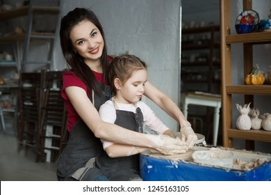 mother and child daughter making ceramic pot on pottery wheel in workshop
