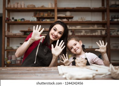 mother and child daughter mold with clay, pottery children at table in workshop
