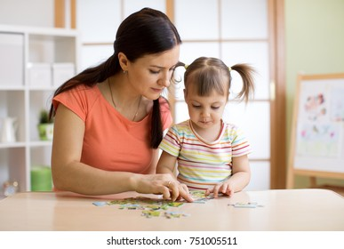 Mother and child daughter playing at home. Woman and kid assembling Jigsaw Puzzle