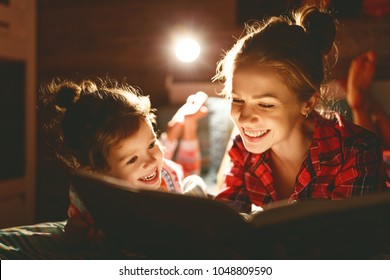 mother and child daughter reading book in bed before going to sleep