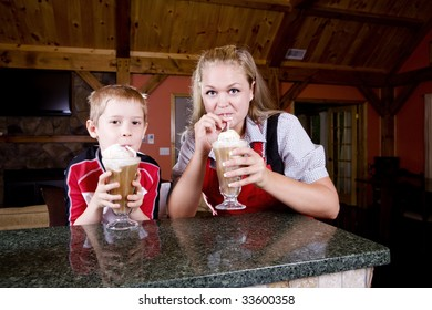 A mother an child drink root beer floats.