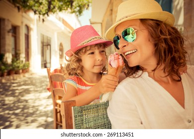 Mother and child eating ice cream in summer cafe outdoors
