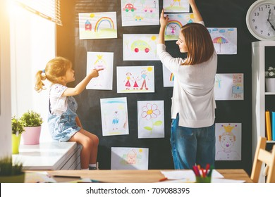 Mother and child girl hang their drawings on the wall