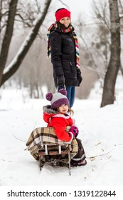 Mother and child girl having fun, playing and laughing on snowy winter walk in nature. Winter season concept.