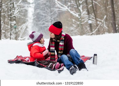 Mother and child girl having fun, playing and drinking tea on snowy winter walk in nature. Winter season concept.
