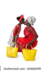 Mother and child girl kissing in traditional red clothing with yellow wicker tote bags. Isolated on the white studio background