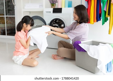 mother and child girl little helper are having fun and smiling while doing laundry at home
