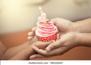 mother and child hand holding birthday cupcake in vintage color tone