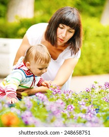 Mother with child happy family outdoors summer time in green garden playing