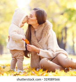 Mother and child having fun in autumn park among yellow leaves