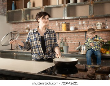 Mother and child having fun in kitchen playing and cooking lunch (preparing food and laughing)