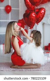 mother with child having fun opening gifts on saint valentine's day. woman with daughter with heart baloons and presents