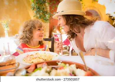Mother and child having fun in summer cafe outdoors