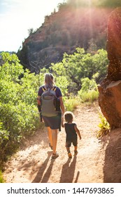 Mother and child hiking together along a scenic mountain trail on a summer day. Lifestyle photo of people outdoors enjoying nature and being active