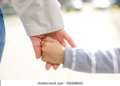 Mother and child holding hands outdoors in closeup