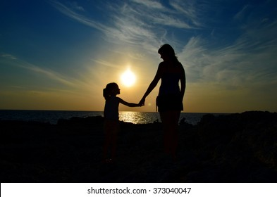 Mother and child holding hands at sunset