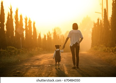 Mother and child holding hands at sunset with copy space, view from the back
