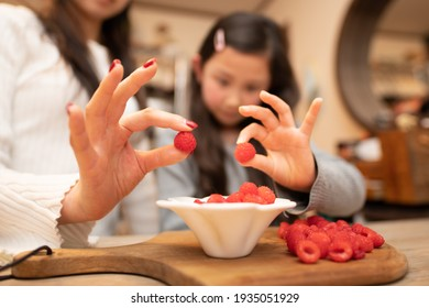 Mother and child holding raspberries