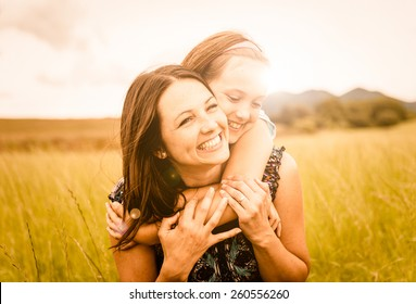Mother and child are hugging and having fun outdoor in nature - photo with lens flare