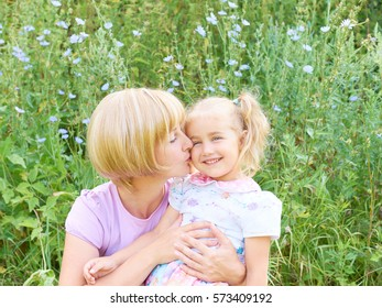 Mother and child are hugging and having fun outdoor in nature on the green grass.