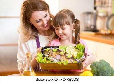 mother and child jolly look at prepared dish of fish in kitchen