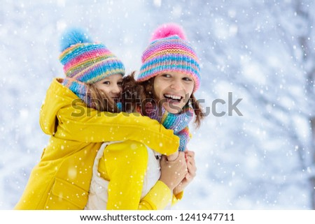 Mother and child in knitted winter hats play in snow on family Christmas  vacation. Handmade 08807a7ac44e