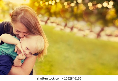 mother and child laughing and playing in the summer on the nature background
