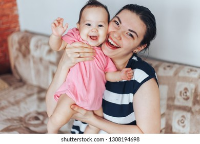 Mother and child on a bed. Mom and baby girl playing in sunny bedroom. Parent and little kid relaxing at home. Family having fun together. mothers day motheriny