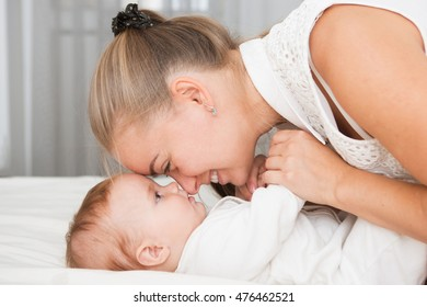 Mother and child on a white bed. Mom and baby  in diaper playing in sunny bedroom. Parent and little kid relaxing at home. Family having fun together.