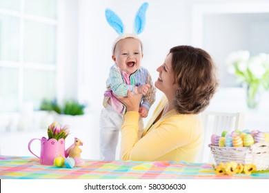 Mother and child painting colorful eggs. Mom and baby with bunny ears paint and decorate Easter egg. Parent and kid play indoors in spring. Decorated home and spring flowers. Family celebrating Easter
